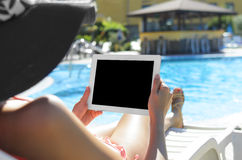 Woman with tablet at swimming pool Royalty Free Stock Images