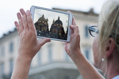 Woman with tablet taking picture to twin churches Royalty Free Stock Image