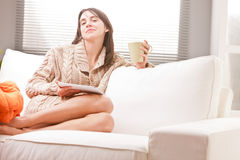 Woman with tablet and tea on sofa in living room Royalty Free Stock Photos