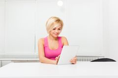 Woman with tablet touch screen pad sitting table Royalty Free Stock Photo
