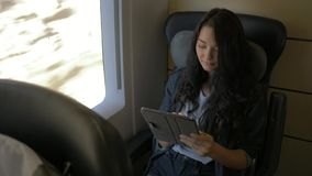 Woman with tablet in train stock video footage
