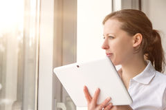 Woman with tablet on a window Royalty Free Stock Image