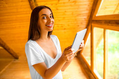 Woman with tablet in the wooden house Stock Photography