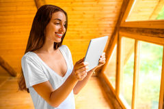 Woman with tablet in the wooden house Stock Photo