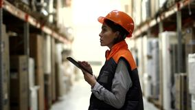 Woman with tablet working in storage. Side view of woman looking up and comparing with list on digital tablet in warehouse