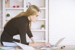 Woman on tabletop using laptop Royalty Free Stock Images