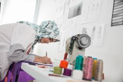 Woman tailor working. Woman tailor creating beautiful clothing in her office Stock Photo