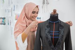 Woman tailor in office. Woman tailor preparing to create beautiful clothing in her office Stock Image
