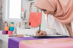 Woman tailor in office. Woman tailor preparing to create beautiful clothing in her office Stock Photo