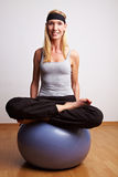 Woman in tailor seat on gym ball Stock Photography