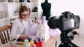 A woman tailor is filming a sewing tutorial with a camera