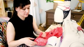 Woman tailor sews lace sexy lingerie in a sewing studio. Fashion style