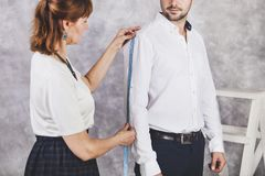 Woman tailor takes measures with male models. Fashion designer s. Woman tailor takes measures with male models. Mid section portrait of tailor fitting bespoke Royalty Free Stock Photo