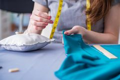 Woman tailor working on a clothing sewing stitching measuring fa Stock Photos