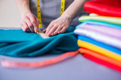 Woman tailor working on a clothing sewing stitching measuring fa Royalty Free Stock Photos