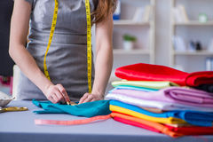 Woman tailor working on a clothing sewing stitching measuring fa Royalty Free Stock Image