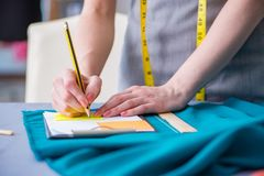 Woman tailor working on a clothing sewing stitching measuring fa Stock Images