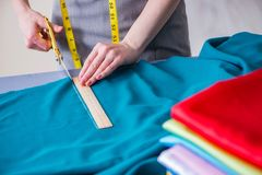 Woman tailor working on a clothing sewing stitching measuring fa Stock Photography