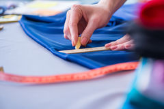 Woman tailor working on a clothing sewing stitching measuring fa Royalty Free Stock Images