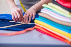 Woman tailor working on a clothing sewing stitching measuring fa Royalty Free Stock Photography