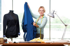 The woman tailor working on new clothing Stock Images