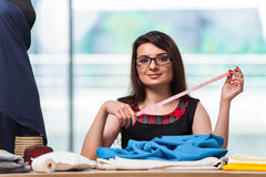 The woman tailor working on new clothing Stock Image