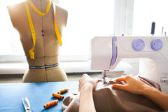 Woman tailor working on sewing machine. Hands. close up. Tailoring. Details. Close up royalty free stock photo
