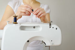 Woman tailor working on sewing machine. Silk thread passed. Royalty Free Stock Images