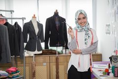 Woman tailor working. Woman tailor creating beautiful clothing in her office Royalty Free Stock Images