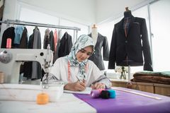Woman tailor working. Woman tailor creating beautiful clothing in her office Royalty Free Stock Image