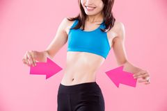 Woman show her waist. Woman take arrow and show her waist on the pink background stock photography
