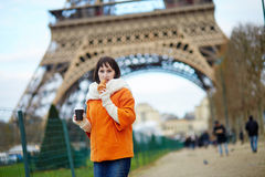 Woman with take-away coffee and croissant near the Eiffel tower Stock Photo
