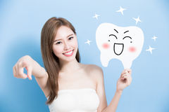 Woman take cute tooth. And introduce on blue background Royalty Free Stock Photos