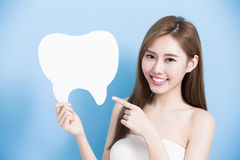 Woman take cute tooth. And show something to you on blue background stock photography