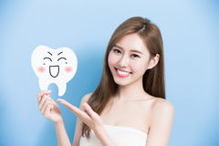 Woman take cute tooth. And show something to you on blue background Stock Photo