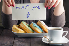 Woman take donuts and hold message eat me Royalty Free Stock Images