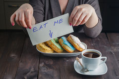 Woman take donuts and hold message eat me Royalty Free Stock Image