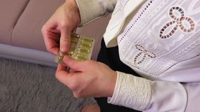Woman take fish oil capsule out of the pack. In room stock video