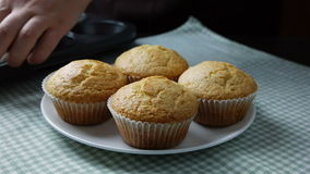 Woman take fresh baked muffins out of muffins tin and place them on plate stock video footage
