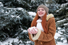 Woman take a handful snow in winter park at day. Fir trees with snow. Royalty Free Stock Images