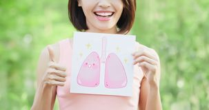 Woman take health lung billboard. And thumb up with green background Royalty Free Stock Images
