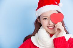 Woman with merry christmas. Woman take heart card with merry christmas on the blue background Royalty Free Stock Photo