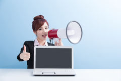 Woman take microphone shouting happily. Business woman take microphone shouting happily and show computer to you with isolated on blue background, asian Stock Photography