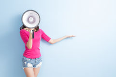 Woman take microphone. And show something to you on blue background royalty free stock photos
