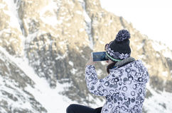 Woman, take a photo with mobile, backgroung from mountains Stock Photography