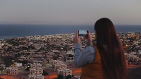 Woman take picture of the sea by smartphone in the evening close-up, Woman stay on top of the mountain and looking Into