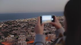 Woman take picture of the sea by smartphone in the evening. Woman stay on top of the mountain and looking Into Horizon