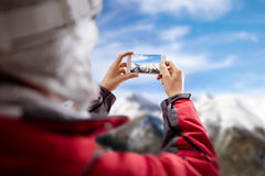 Woman take picture of winter landscape Stock Photography