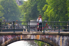 Woman take pictures standing on bridge in Amsterdam. Royalty Free Stock Image