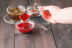 Woman take raspberry jam from glass jar. On wooden table Stock Photography